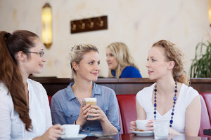 Three attractive stylish young female friends drinking coffee together and chatting in a cafe